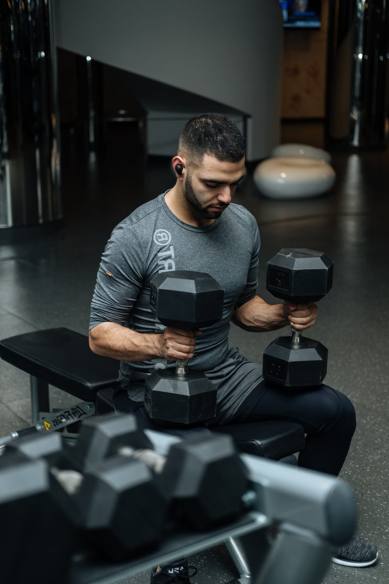 Man Sitting on Weight Bench with Dumbbell