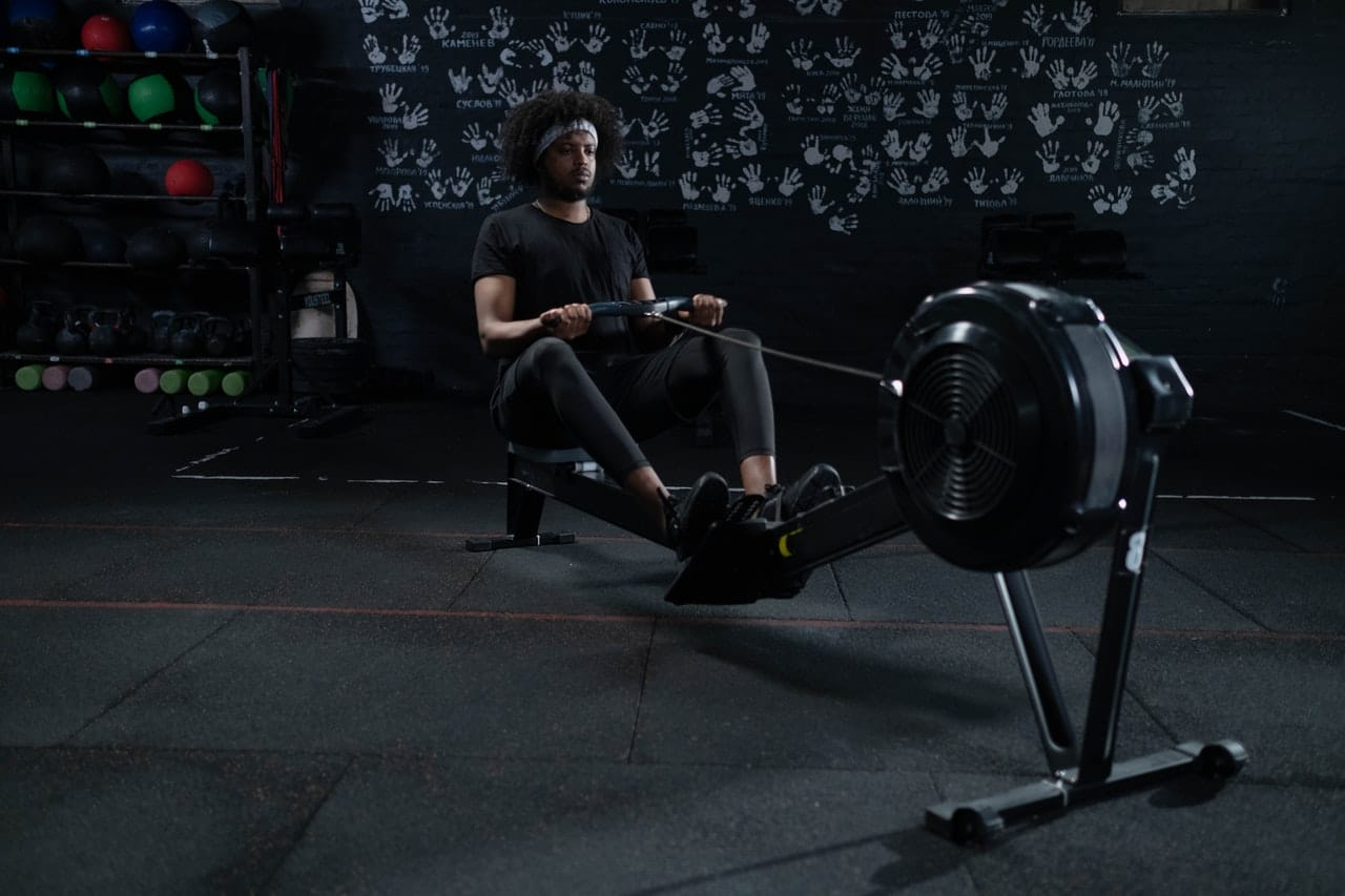 Man in Black Exercising with a Rowing Machine